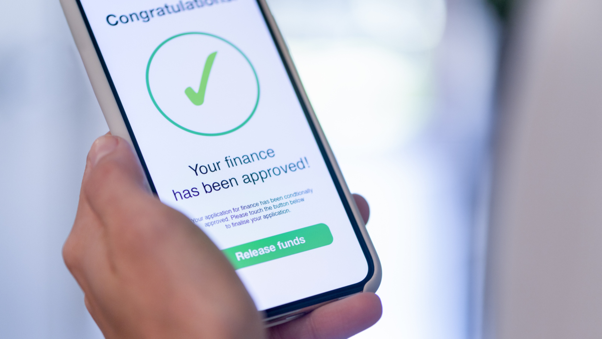 Woman holding a mobile phone with loan application approval. She is being prompted to press a button to release the funds. Close up.